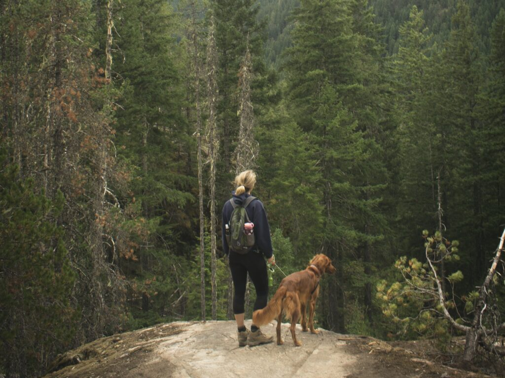 A Woman hiking with her dog